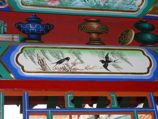 Painting of swallows on building eave
